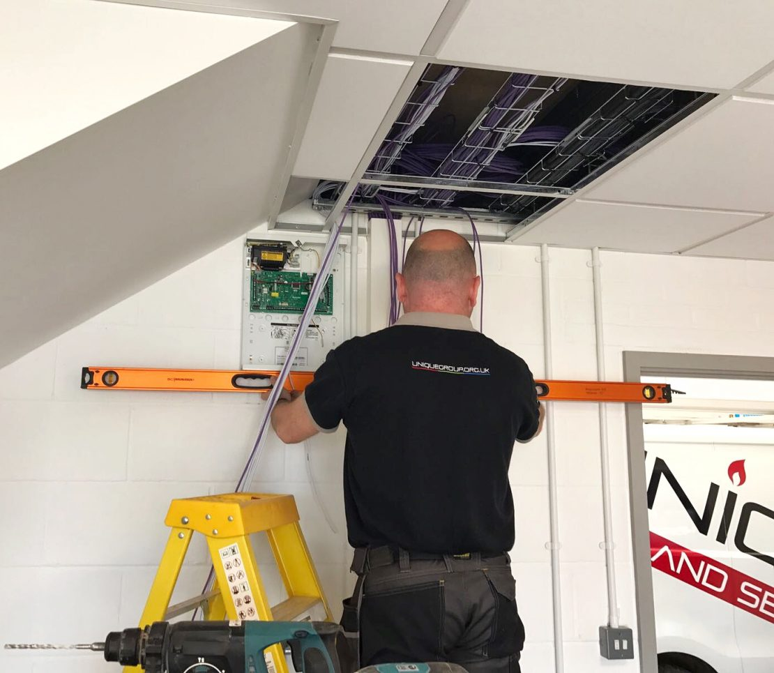 Unique Alarm Engineer completing a system service maintenance on an intruder